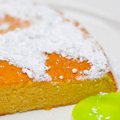 A piece of the amazing butter sponge cake served on a white plate with a green spoon