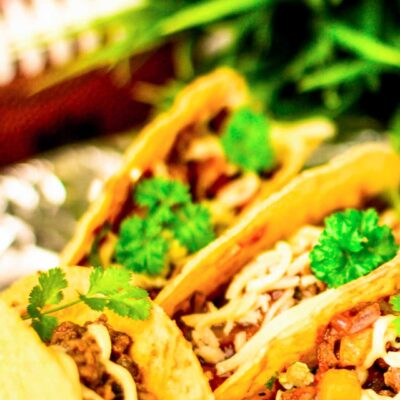 Four Tailgate Tacos with a football and a pot full of green grass blurred in the background
